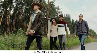 Young friends walking on countryside road - Group of young...