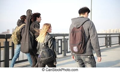 Young friends walking on the quay and talking. Mid shot