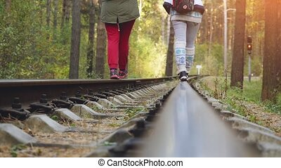 Young friends walking together with backpackers on railroad in pines forest in slowmotion. 1920x1080