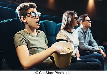 Young friends watching 3d movie in cinema