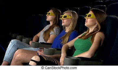 Young friends watching a film at the cinema, 3d glasses