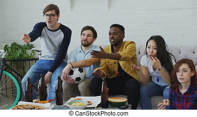 Young friends watching football game on TV together at home...