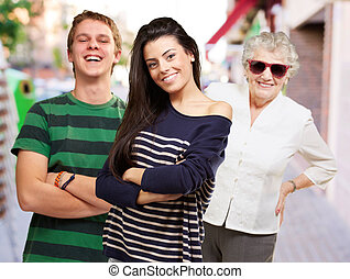 young friends with grandmother smiling at street
