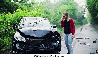 Young frustrated woman making a phone call after a car accident.