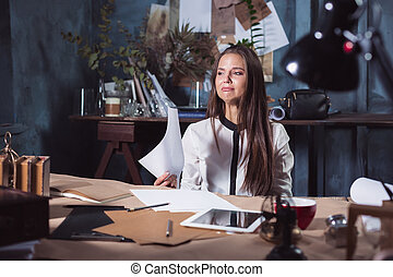 Young frustrated woman working at office desk in front of laptop