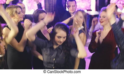 Young fun party people dancing at the night club