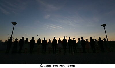 Young fun party people dancing with the sunset and sky in clouds on background