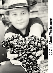 Young funny boy posing with bunch of grapes in hands, black and white