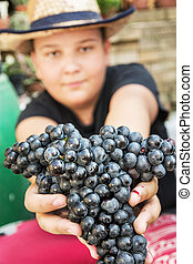 Young funny boy posing with bunch of grapes in hands, vintage theme