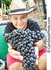 Young funny boy with bunch of grapes in hands, vintage theme
