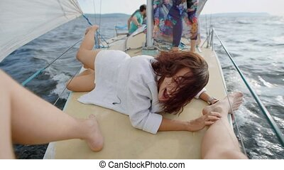 young funny brunette is on a board of small sailboat is holding legs of her boyfriend, in summer holidays