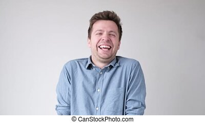 Young funny caucasian man laughing on his friend joke. ...