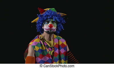 Young funny clown quarreling with somebody