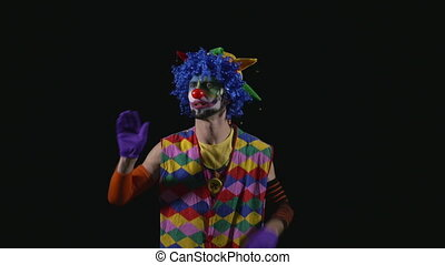 Young funny clown shouting and using a megaphone