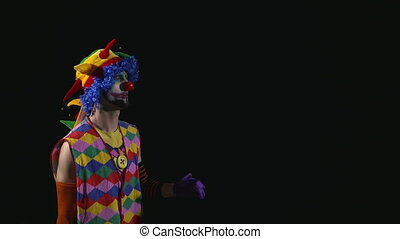 Young funny clown using a megaphone and shouting