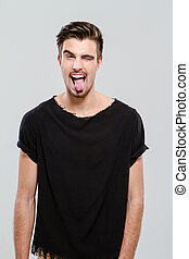 Young funny guy winking and sticking out his tongue