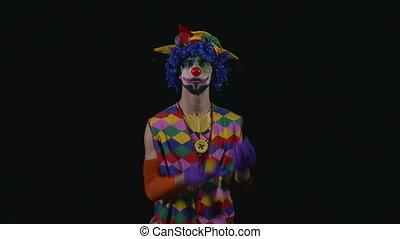 Young funny hilarious clown juggling