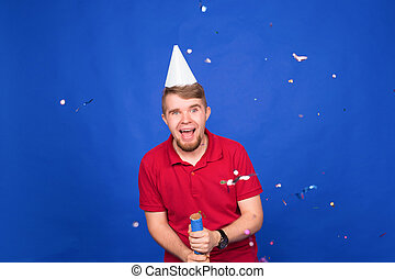 Young funny man celebrating new year and christmas party with confetti