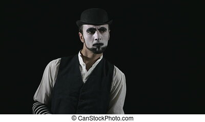 Young funny mime listening to something