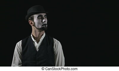 Young funny mime showing and pointing at something and approving