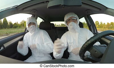 Young funny scientists sitting in car dressed in hazmat wear...