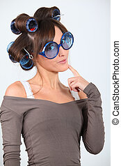Young funny woman with hair-curlers