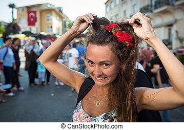 Young funny woman with roses in hair stands on the city square
