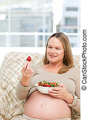Young future mom with strawberries