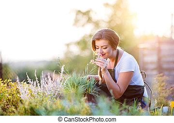 Young gardener in garden smelling flower, sunny nature