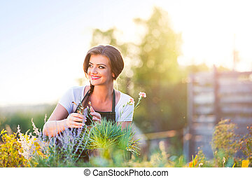 Young gardener in garden with various plants, sunny nature