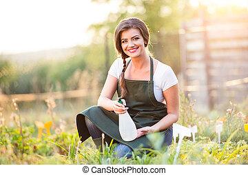 Young gardener in green apron sprinkling plants, garden