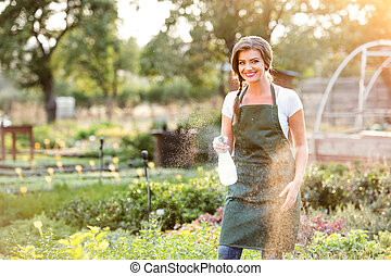 Young gardener in green apron sprinkling plants, garden