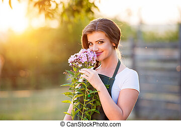 Young gardener in her garden smelling flowers, sunny nature