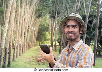 Young gardener man holding digital tablet in garden
