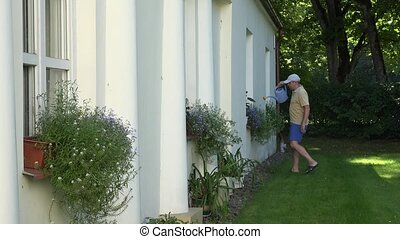 young gardener man in shorts watering flower pots on garden house window sills.