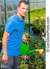 young gardener posing with a watering can in the garden flowers