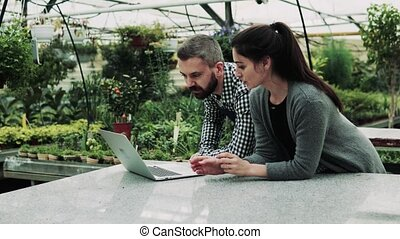 Young gardeners with laptop in a large greenhouse. - Young...