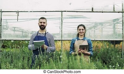 Young gardeners with tablet in a large greenhouse.