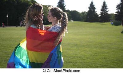 Young gay couple standing wrapped in lgbt flag