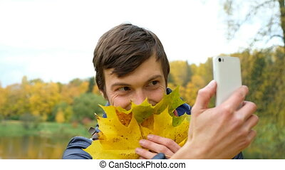 Young gay man fooling around and Hamming, laughing and making selfie with autumn leaves on white your modern smartphone in a Park.
