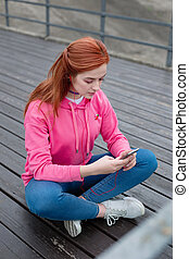 Beautiful red haired woman using her smartphone
