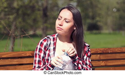 Young girl 20s drinking water from bottle in park