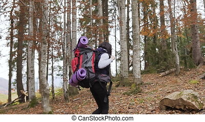 Young girl - a tourist walking in the woods with a red backpack and fastened violet carimate she sits itself up to rest on a wooden stump. Concept of autumn forest