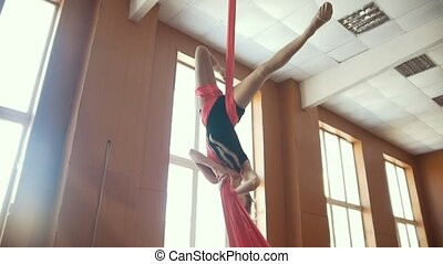 Young girl acrobat shows flexibility on gymnastic cloth,...