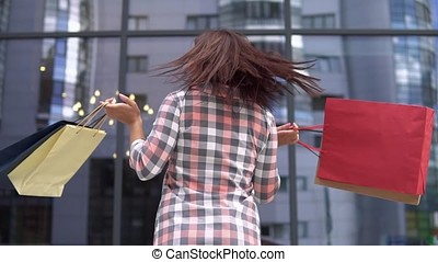 Young girl after shopping with bags in the hands near the shopping center having a good mood. slow motion. HD