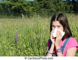 young girl allergic to pollen while blowing her nose in the middle of the meadow in spring