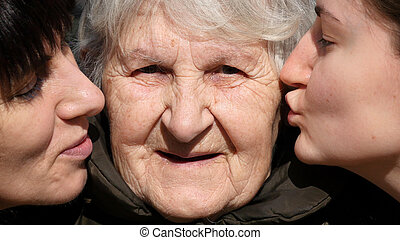 Young girl and adult woman kissing grandmother on cheeks, Granny smiling and looking to the camera. Three family generations. Grandmother, mother and granddaughter.