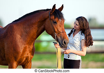 Young girl and bay horse outdoor.