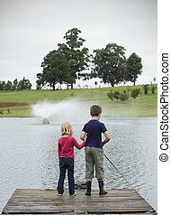 Young girl and boy fishing on wooden pier
