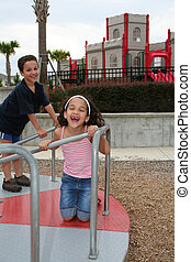 Young Girl and boy on Playground - Young girl and boy...